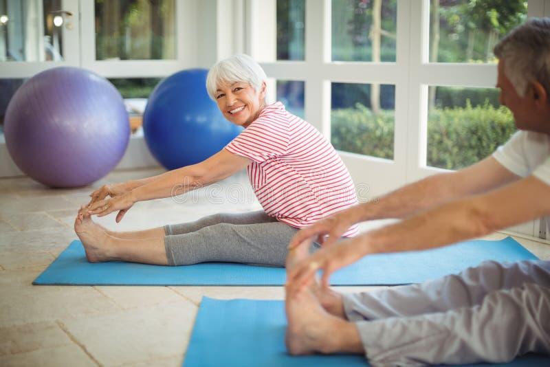 Ältere Paare, die Übung auf Übungsmatte ausdehnend durchführen stockfotos