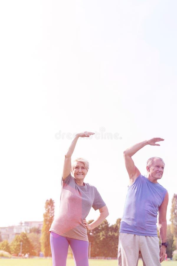 Ältere Paare, die Übung im Park gegen Himmel ausdehnend tun lizenzfreies stockbild