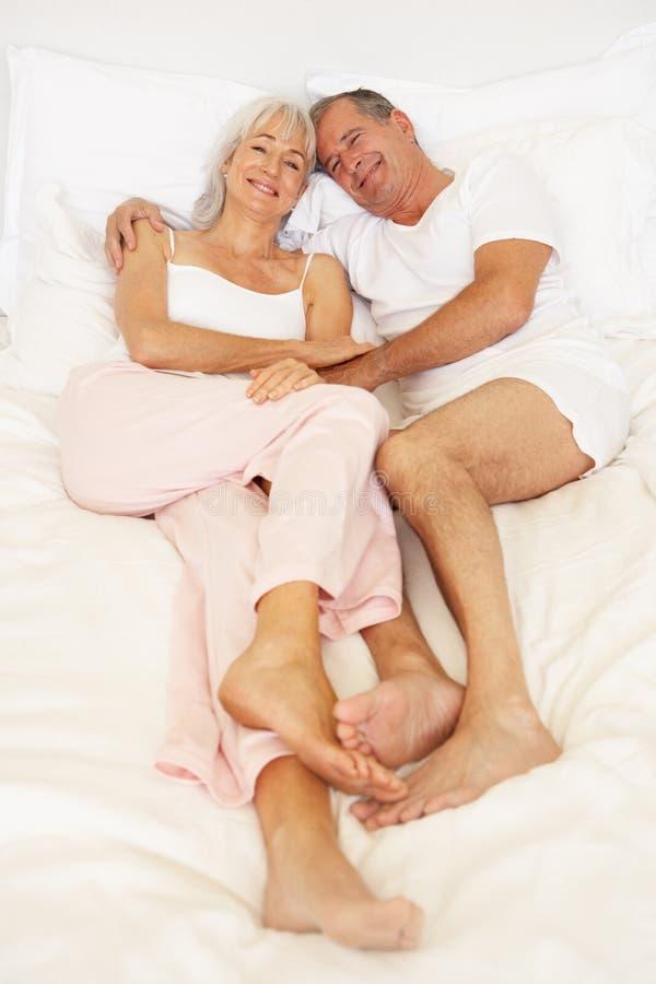 Ältere Paare, die auf Bett sich entspannen lizenzfreies stockbild