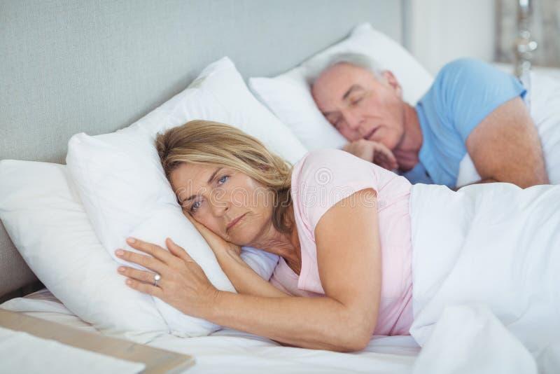 Ältere Paare, die auf Bett sich entspannen stockbilder