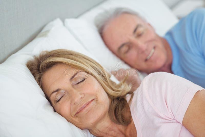 Ältere Paare, die auf Bett stillstehen stockfotos