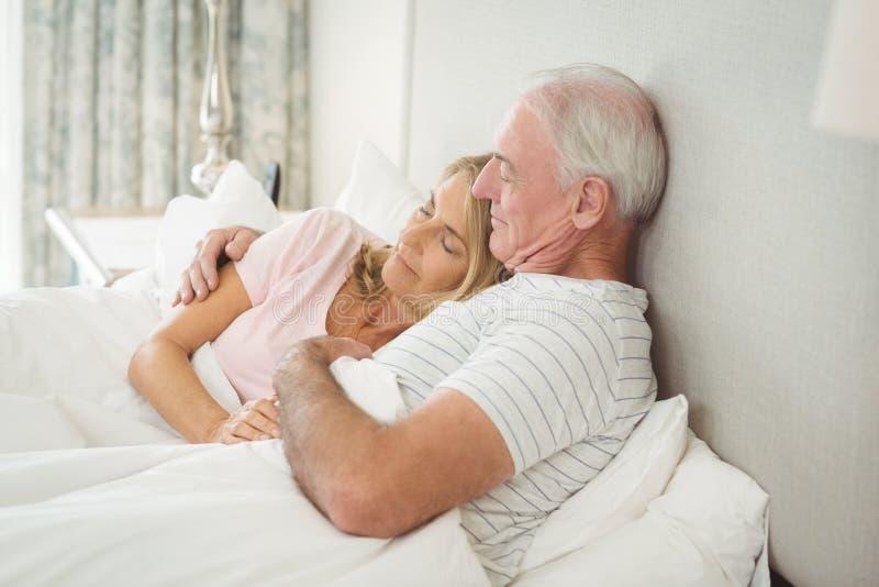 Ältere Paare, die auf Bett umfassen stockbild