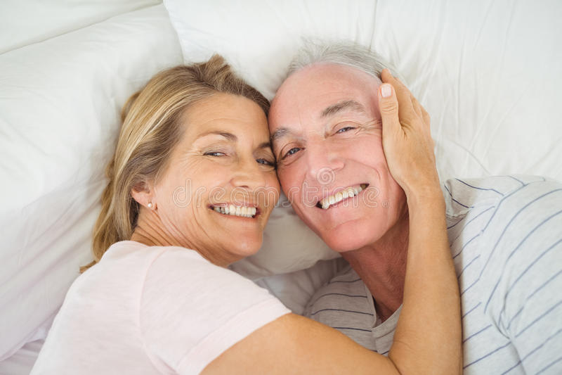 Ältere Paare, die auf Bett umfassen lizenzfreies stockbild