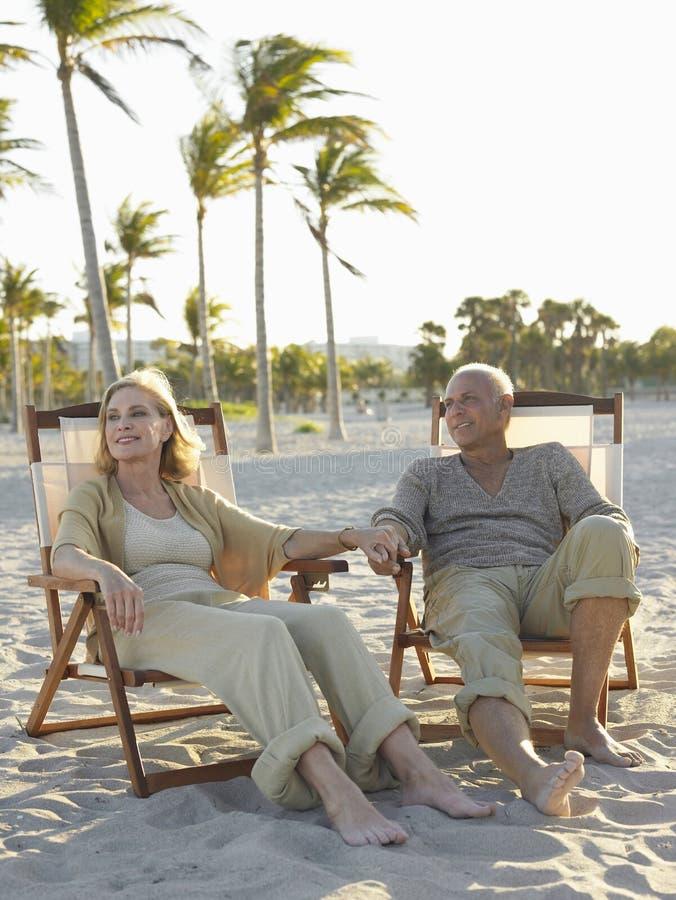 Ältere Paare, die auf Deckchairs am Strand sich entspannen stockfoto