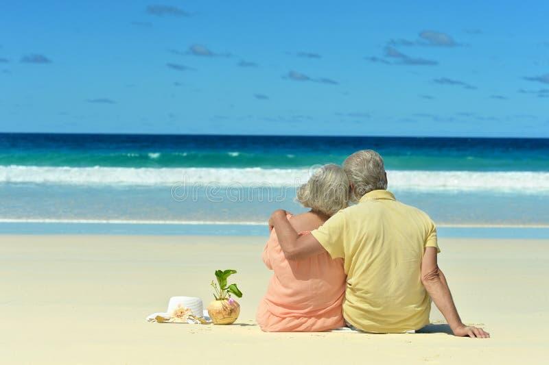 Ältere Paare, die auf dem Ufer sitzen lizenzfreie stockfotografie