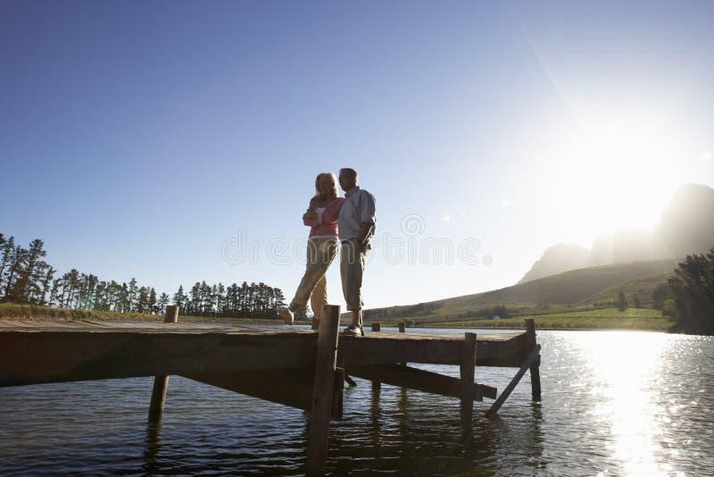 Ältere Paare, die auf der hölzernen Anlegestelle heraus schaut über See stehen lizenzfreie stockbilder
