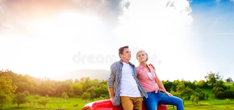Ältere Paare, die auf der Rückseite des roten Kleintransporters sitzen stockbilder