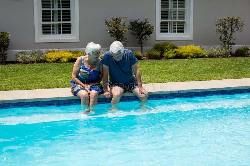 Ältere Paare, die auf einander am Poolside einwirken stockfotos