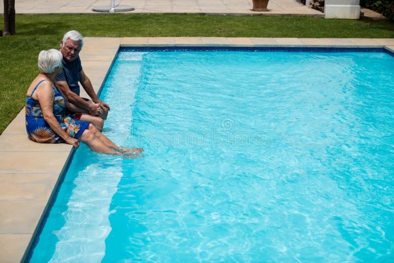 Ältere Paare, die auf einander am Poolside einwirken lizenzfreie stockfotos