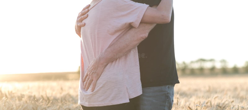 Ältere Paare, die auf einem Weizengebiet, Sonnenlichteffekt sich umfassen stockfotos