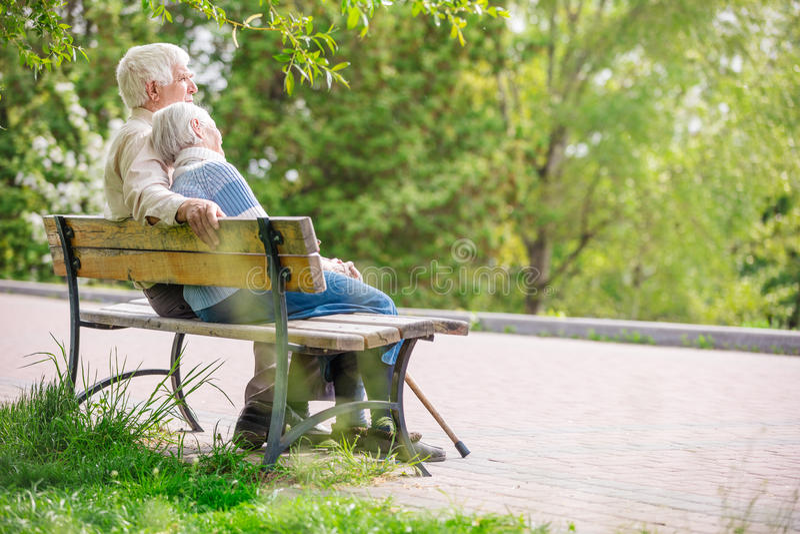Ältere Paare, die auf einer Bank stillstehen lizenzfreie stockbilder