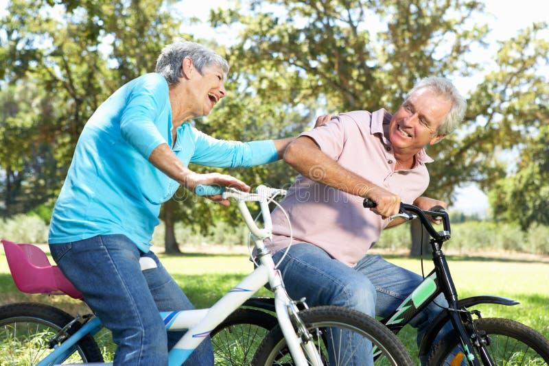 Ältere Paare, die auf Fahrrädern der Kinder spielen lizenzfreies stockbild
