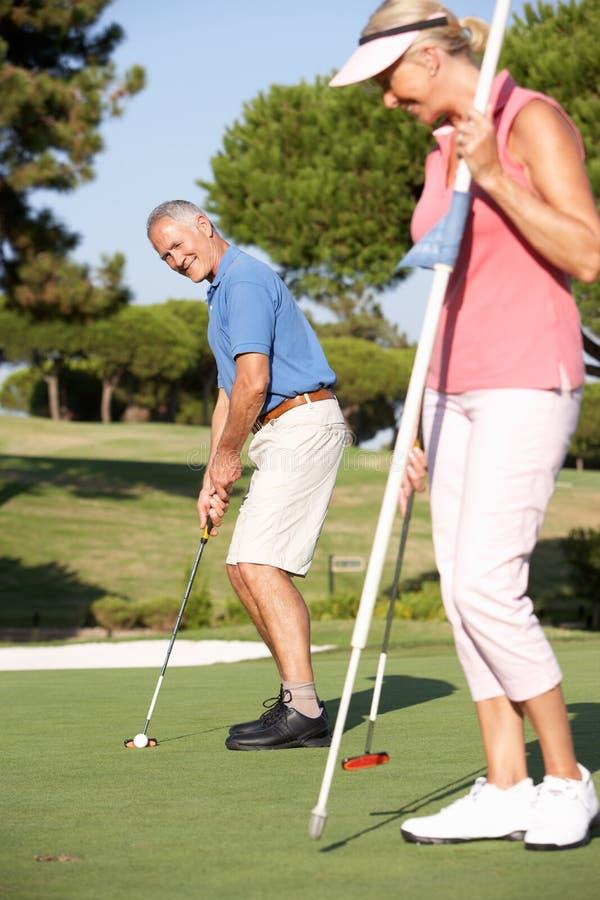 Ältere Paare, die auf Golfplatz Golf spielen lizenzfreies stockbild