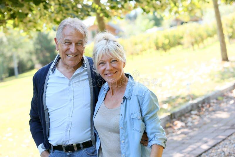 Ältere Paare, die auf sonnige Tage gehen lizenzfreies stockfoto