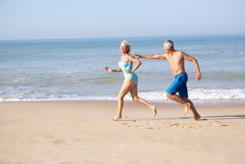 Ältere Paare, die auf Strand laufen lizenzfreie stockfotos