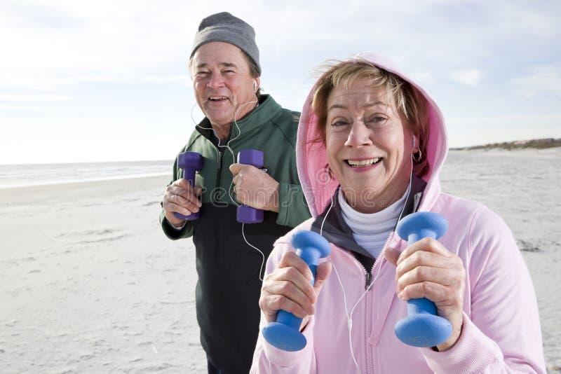 Ältere Paare, die auf Strand trainieren lizenzfreie stockfotografie