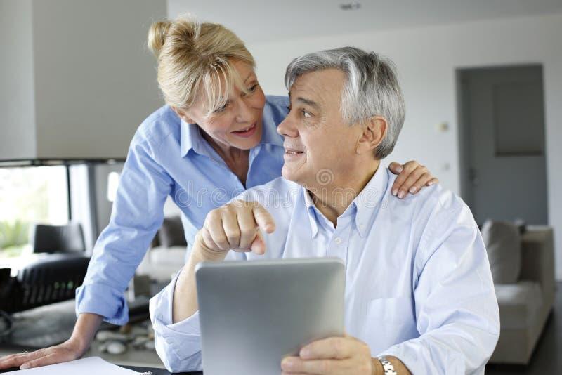 Ältere Paare, die Bankkonto auf Tablette betrachten stockfoto