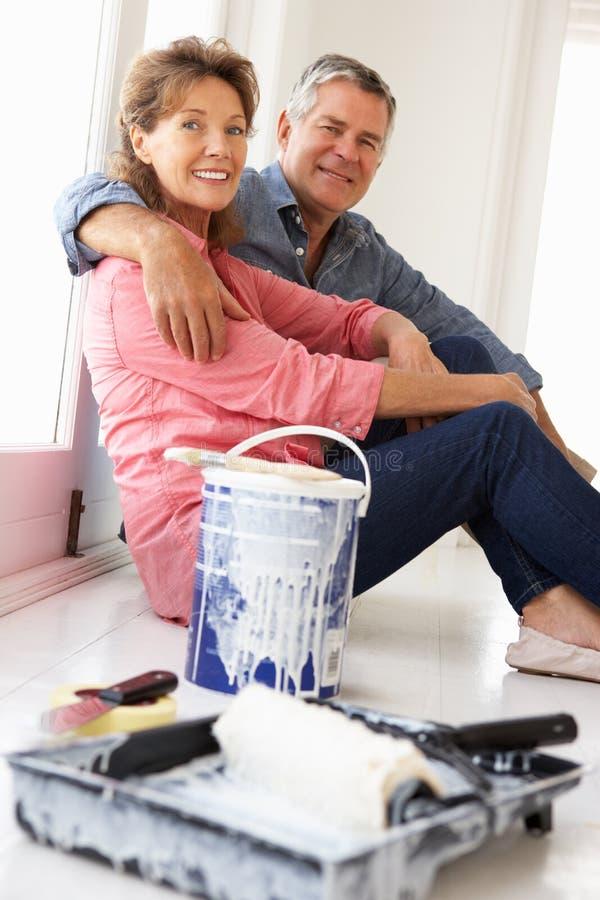 Ältere Paare, die Bruch von der Verzierung des Hauses nehmen stockbild