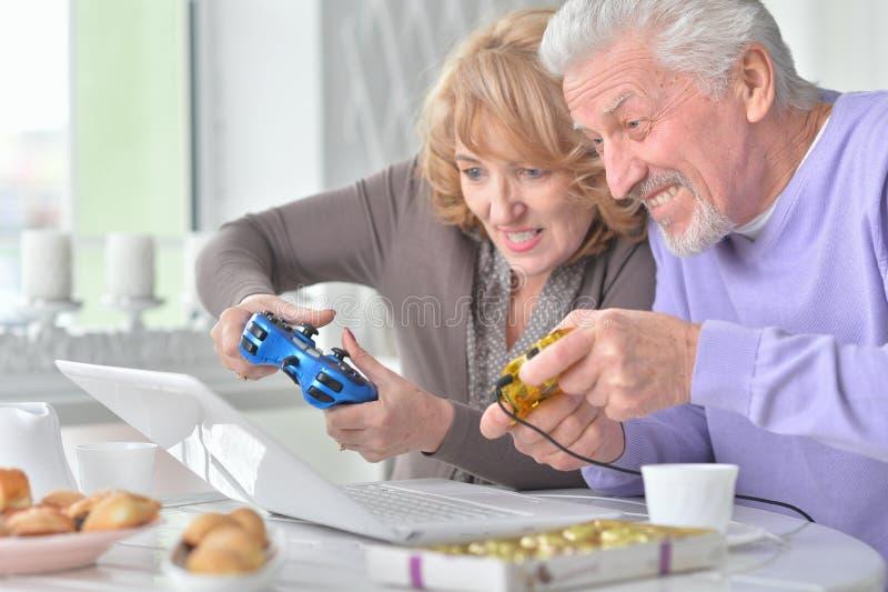 Ältere Paare, die Computerspiel mit Laptop beim Trinken von t spielen stockfotografie