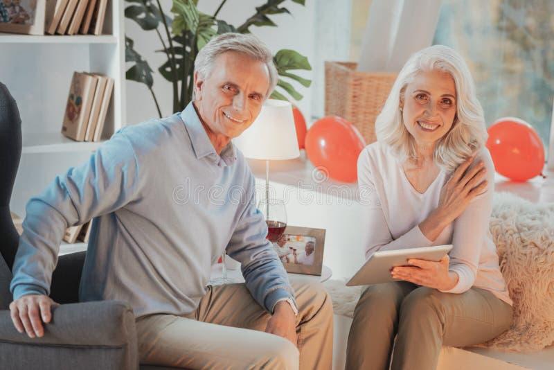Ältere Paare, die in den bequemen Stühlen sitzen und Kamera betrachten stockfoto