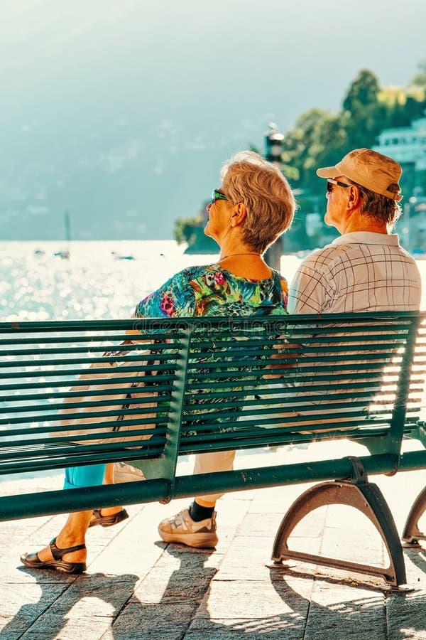 Ältere Paare, die in der Bank in Luxusfremdenverkehrsort Ascona sitzen stockfoto