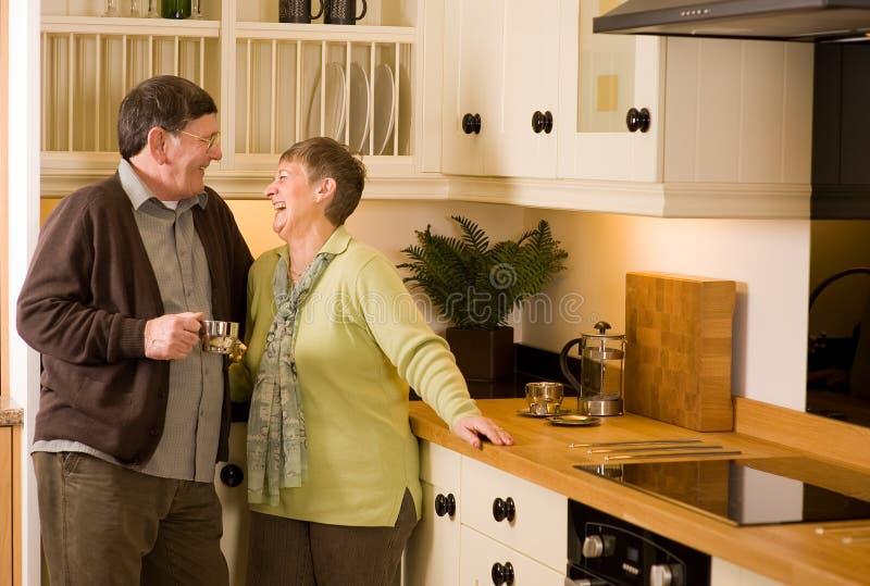 Ältere Paare, die in der Entwerferküche lachen lizenzfreie stockbilder