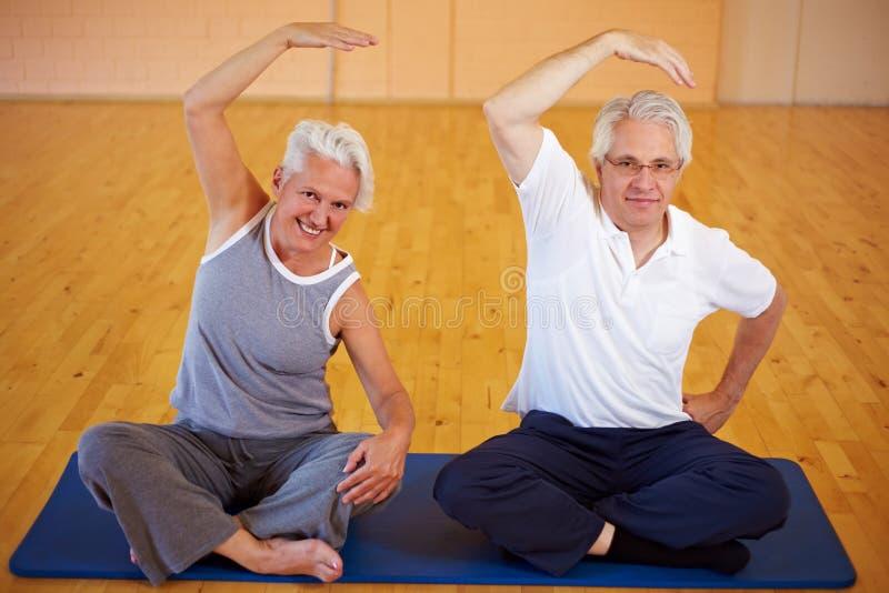 Ältere Paare, die in der Gymnastik trainieren stockbilder
