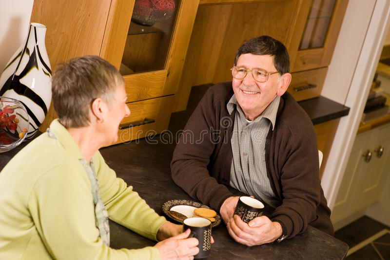 Ältere Paare, die in der Küche sprechen lizenzfreies stockfoto
