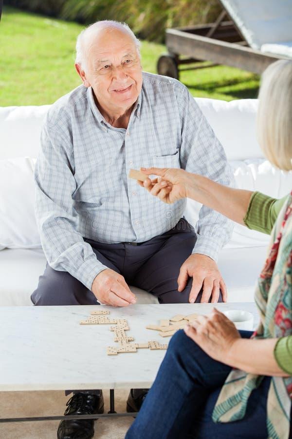Ältere Paare, die Dominos spielen stockbild