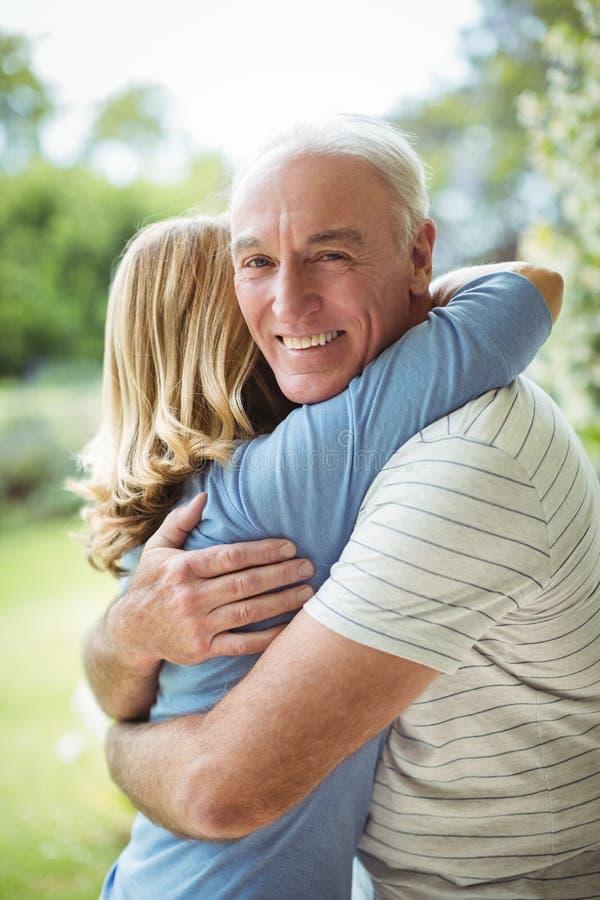 Ältere Paare, die draußen umfassen stockfoto