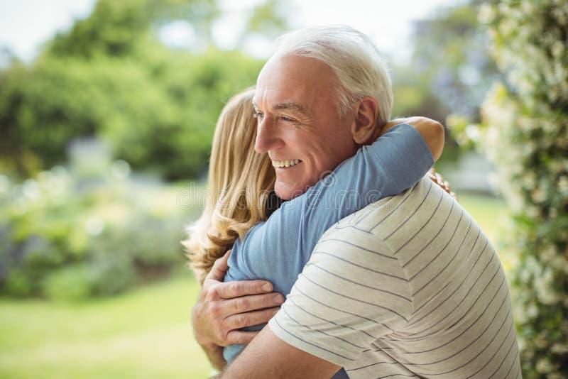 Ältere Paare, die draußen umfassen stockbild