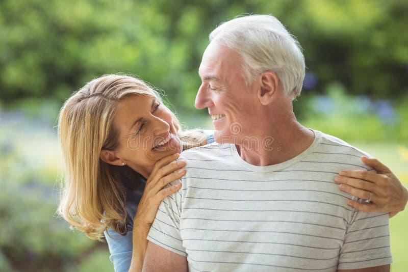 Ältere Paare, die draußen umfassen lizenzfreies stockfoto