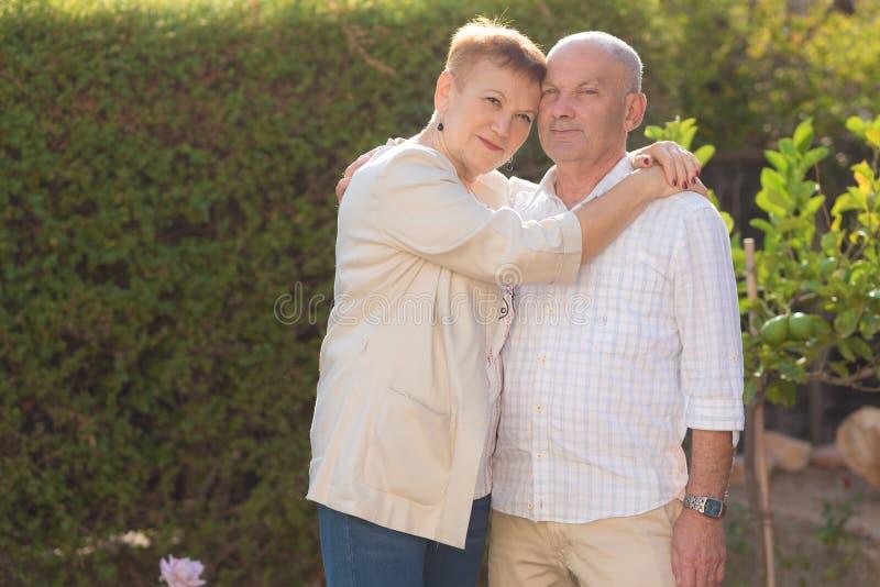 Ältere Paare, die durch den Park am sonnigen Tag sich entspannen lizenzfreie stockfotos