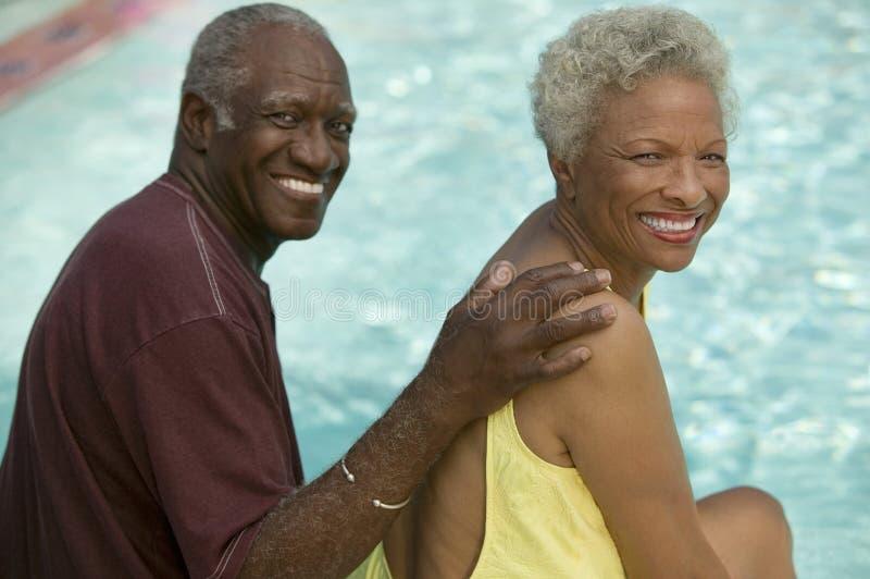 Ältere Paare, die durch Swimmingpoolporträt sitzen. stockbild