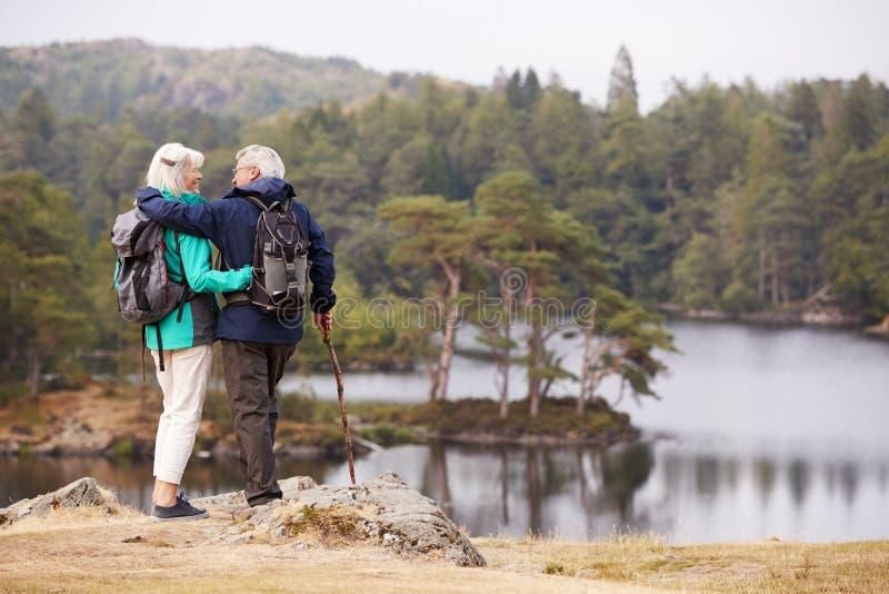 Ältere Paare, die eine Ansicht von den Seen betrachten einander, zurück Ansicht umfassen und bewundern lizenzfreie stockbilder