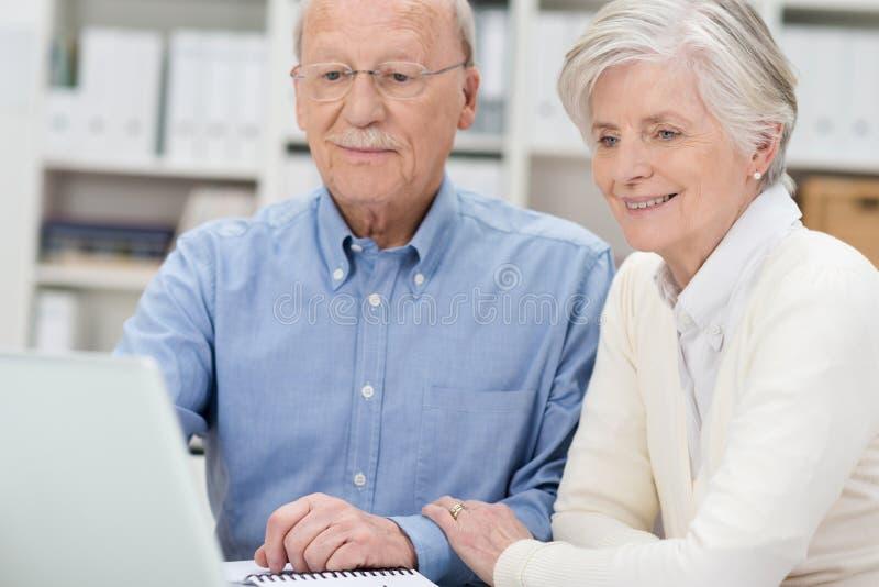 Ältere Paare, die eine Laptop-Computer teilen lizenzfreie stockfotografie