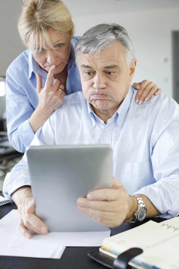 Ältere Paare, die eine Steuererklärung on-line abgeben stockbild