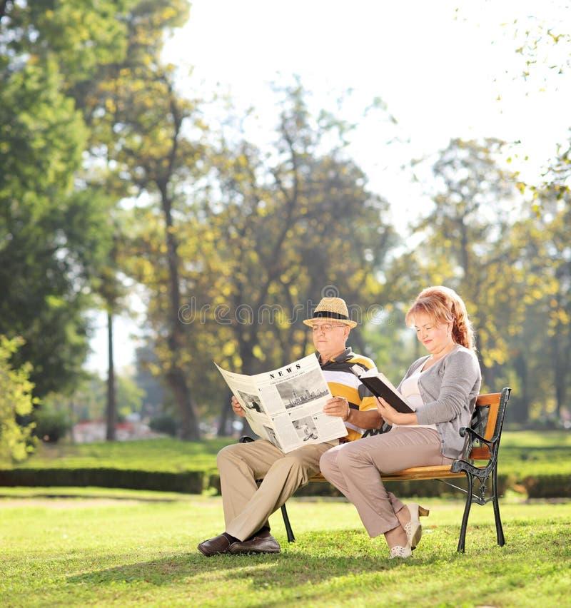Ältere Paare, die an einem schönen Tag im Park sich entspannen lizenzfreies stockbild
