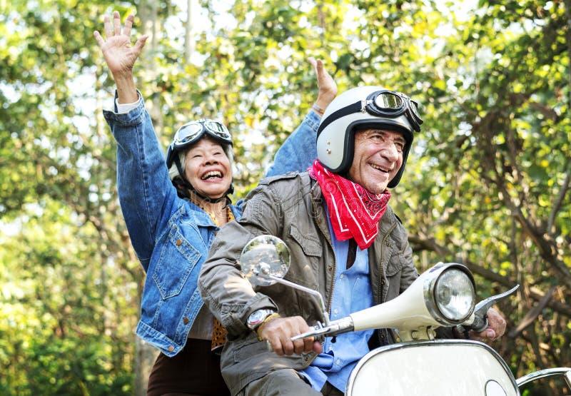 Ältere Paare, die einen klassischen Roller reiten stockfotografie