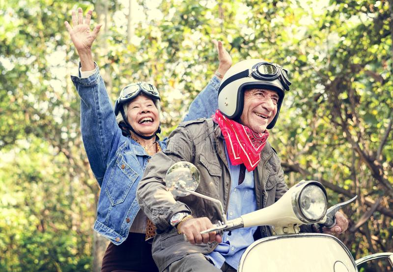 Ältere Paare, die einen klassischen Roller reiten lizenzfreie stockfotos