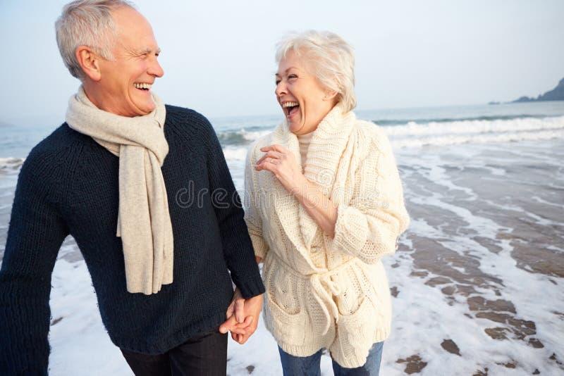 Ältere Paare, die entlang Winter-Strand gehen stockbild