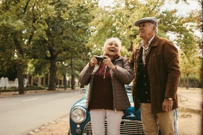 Ältere Paare, die Foto auf Autoreise machen lizenzfreie stockbilder