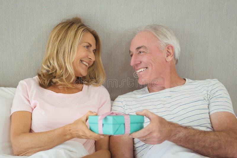 Ältere Paare, die Geschenkbox auf Bett halten lizenzfreie stockfotos