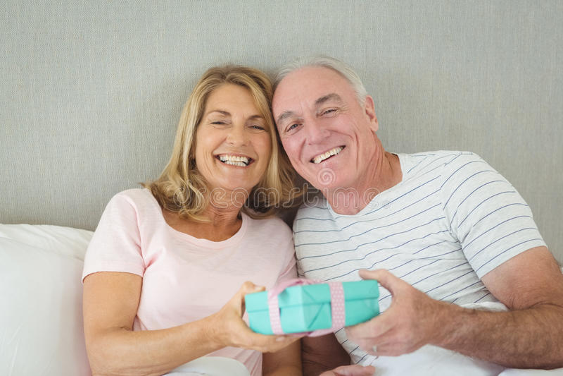 Ältere Paare, die Geschenkbox auf Bett halten lizenzfreies stockbild