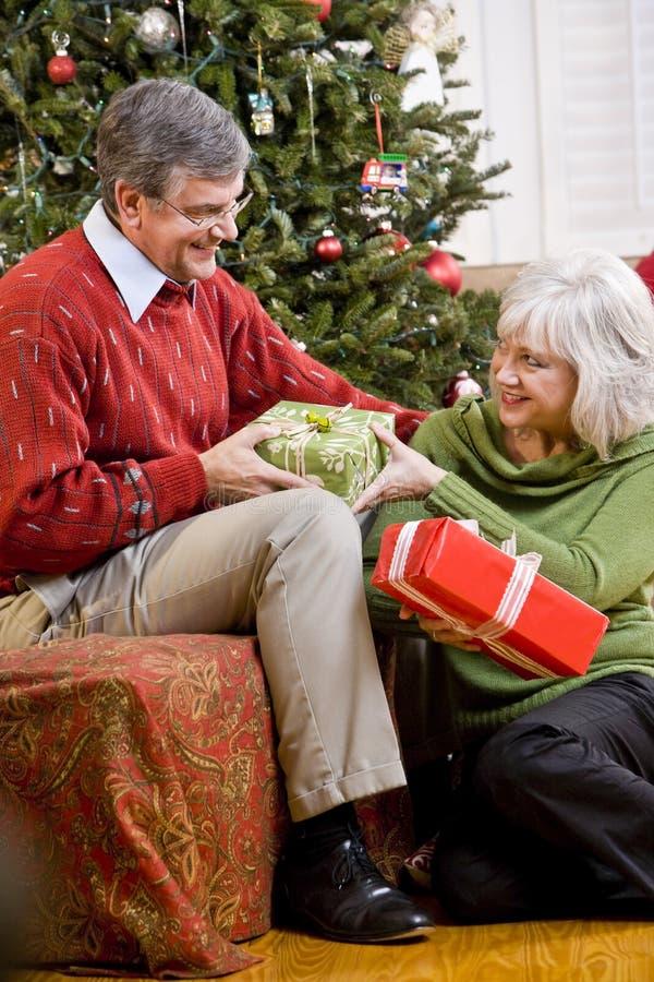 Ältere Paare, die Geschenke durch Weihnachtsbaum austauschen stockbild