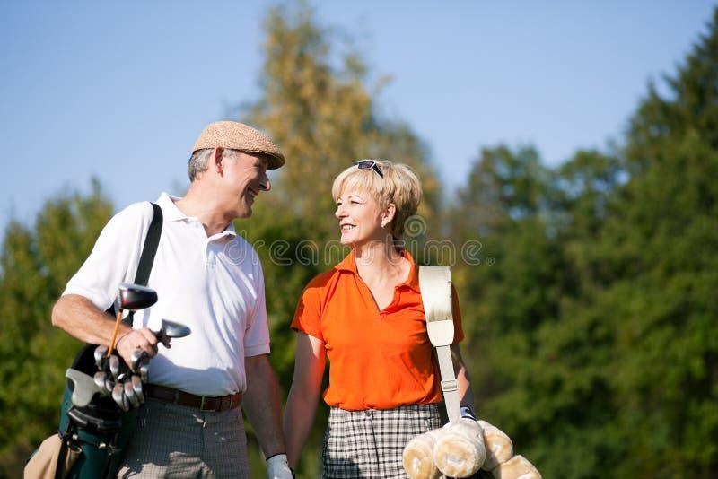 Ältere Paare, die Golf spielen stockbild