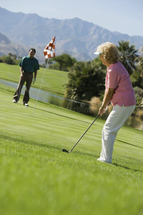 Ältere Paare, die Golf spielen stockfotos