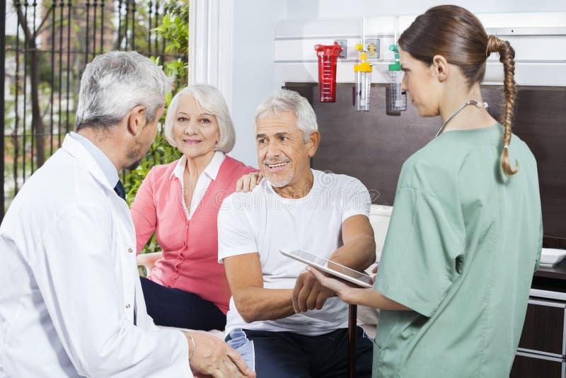 Ältere Paare, die hören, um While Nurse Holding Digital Ta zu behandeln stockbilder