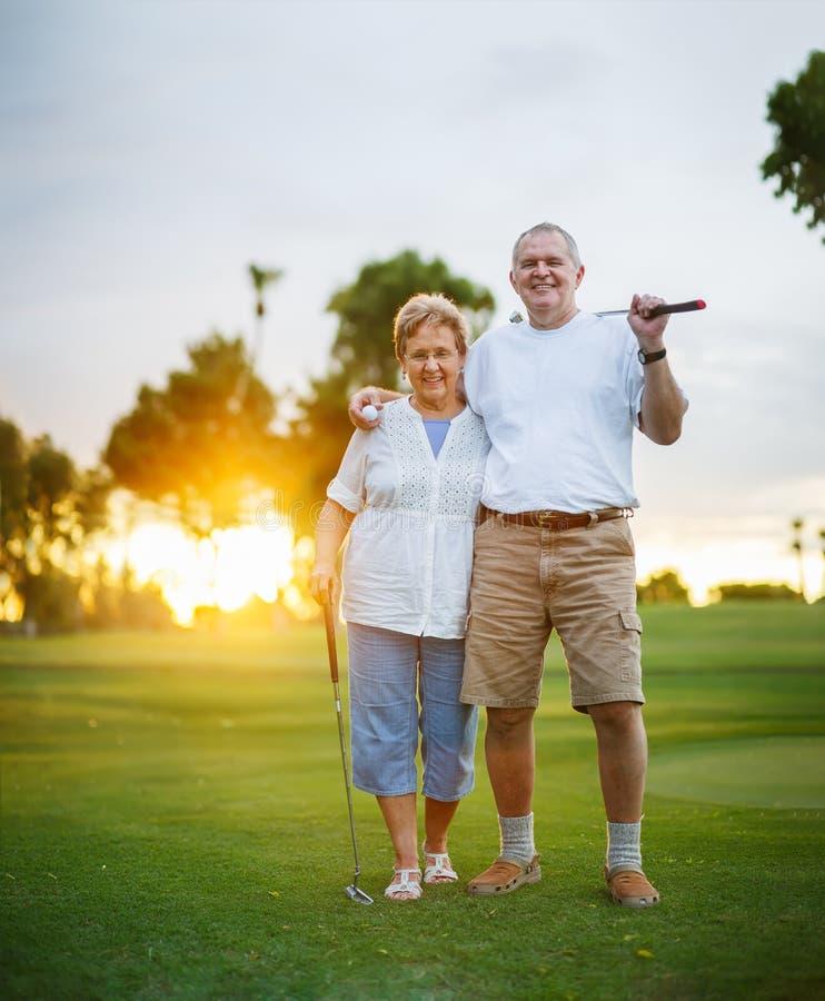 Ältere Paare, die heraus zusammen Porträt des Golfs spielen lizenzfreies stockfoto