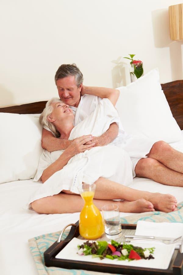 Ältere Paare, die in Hotelzimmer-tragenden Roben sich entspannen stockfotos